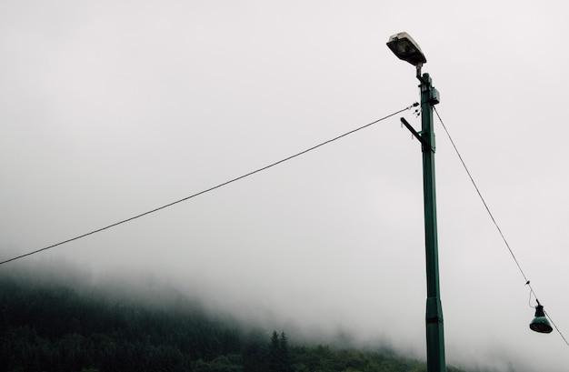 Lampione di metallo in campagna durante una nebbiosa giornata cupa