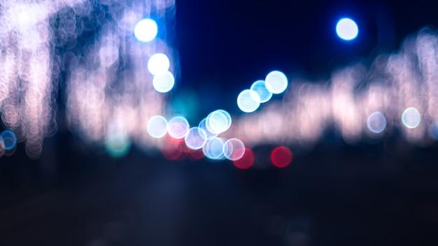 Lampioni notturni sfocati. iluminazioni pubbliche di bokeh dalle automobili nella città.