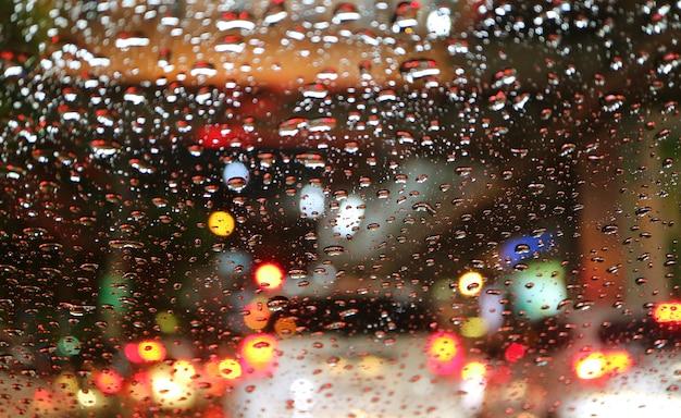 Lampioni stradali e luci posteriori vaghi osservati attraverso le goccioline di acqua sul parabrezza dell'automobile