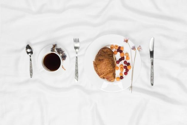 Lampone con croissant; tazza di caffè con forchetta e cucchiaio su priorità bassa strutturata bianca