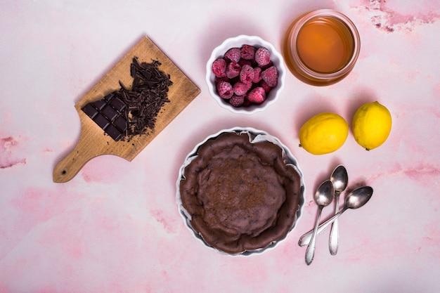 Lampone; limone; olio; barretta di cioccolato con torta preparata fresca e cucchiai su sfondo rosa con texture
