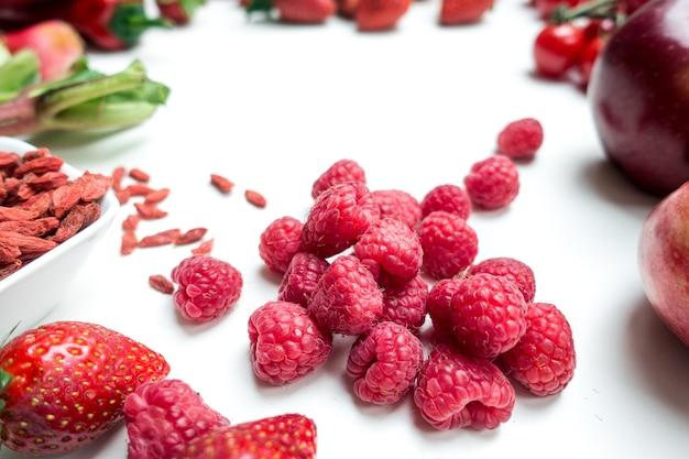 Lamponi e altra frutta e verdura rossa su sfondo bianco_1