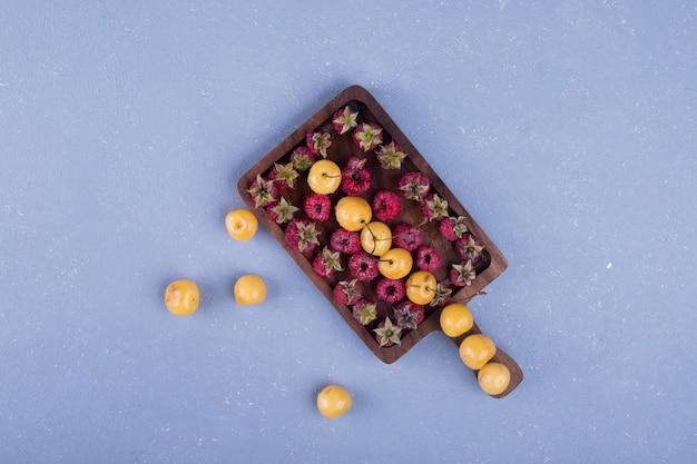 Lamponi e ciliegie in un vassoio di legno al centro