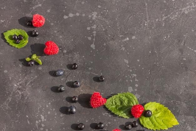 Lamponi e mirtilli succosi freschi con le foglie di menta su un fondo scuro. bacche estive su fondo nero. sano, vegetariano, mangiando, stando a dieta.