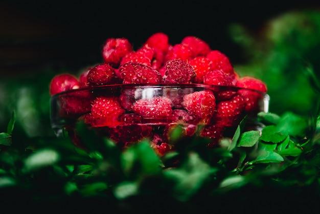 Lamponi in una ciotola di vetro con ramoscelli e foglie su uno sfondo scuro. frutti sani e freschi di stagione da mangiare.