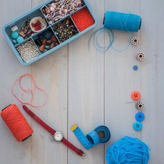 Lana blu; rocchetto di filo; orologio da polso; nastro di misurazione; bottoni e cassa delle perline sulla scrivania in legno