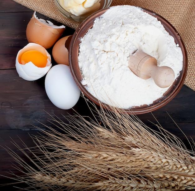 Lanci con le orecchie delle uova della farina di grano e di burro sul concetto d'annata dell'alimento e della bevanda del bordo di legno