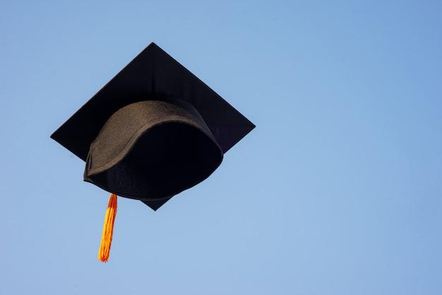 Lancia un cappello nero di laureati nel cielo.