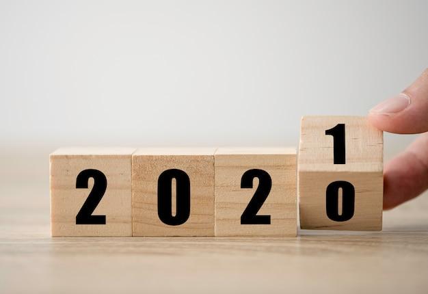 Lanciando a mano blocchi di legno per cambiare gli anni dal 2020 al 2021