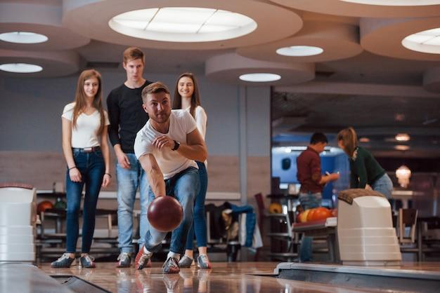 Lanciare la palla. i giovani amici allegri si divertono al bowling durante i fine settimana
