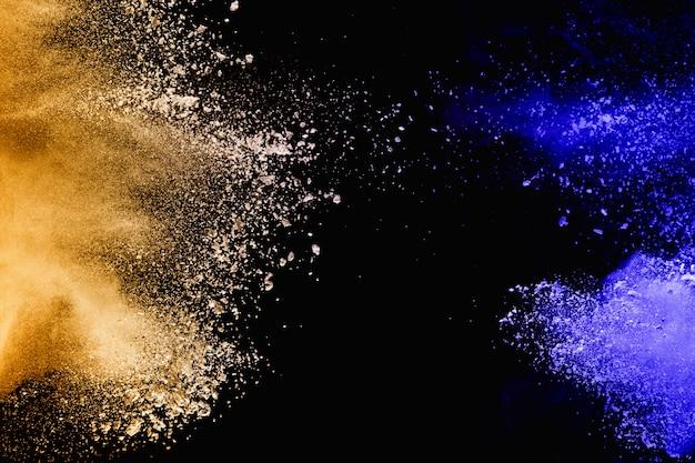 Lanciato spruzzi di particelle di polvere giallo-blu su sfondo.