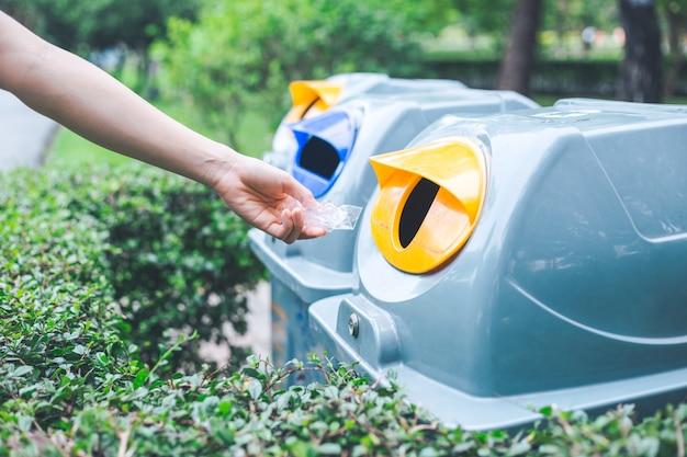 Lancio a mano di una busta di plastica nel cestino.concetti di conservazione ambientale e riscaldamento globale.