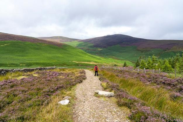 Lanscape di wicklow in una giornata nuvolosa con una ragazza escursionista.