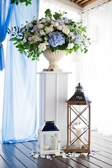 Lanterna araba vintage marocchina in argento con candela incandescente, fiori rose e petali rosa.