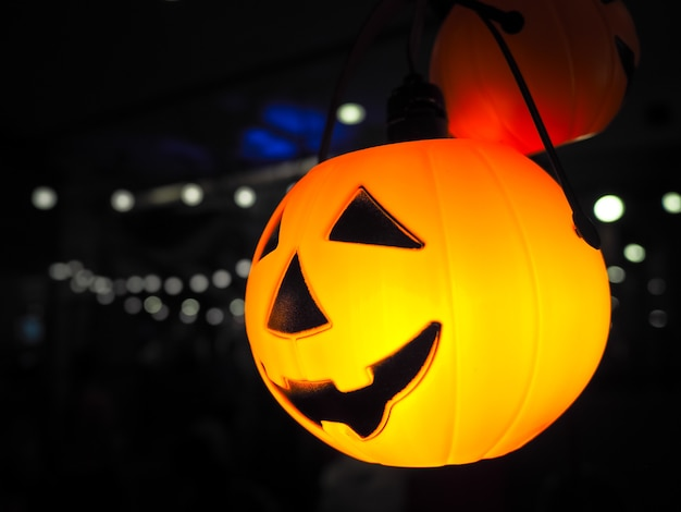 Lanterna della presa della testa della zucca di halloween con illuminazione sopra fondo nero. celebrità di halloween