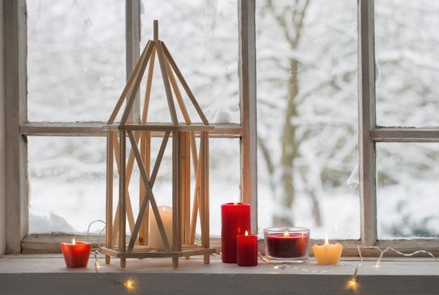 Lanterna di legno sul davanzale sul paesaggio invernale
