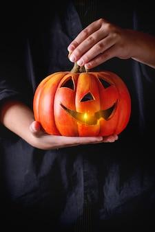 Lanterna di zucca di halloween nelle mani del bambino