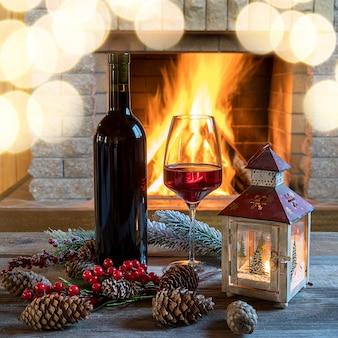 Lanterna e vino rosso con decorazioni natalizie vicino al caminetto accogliente