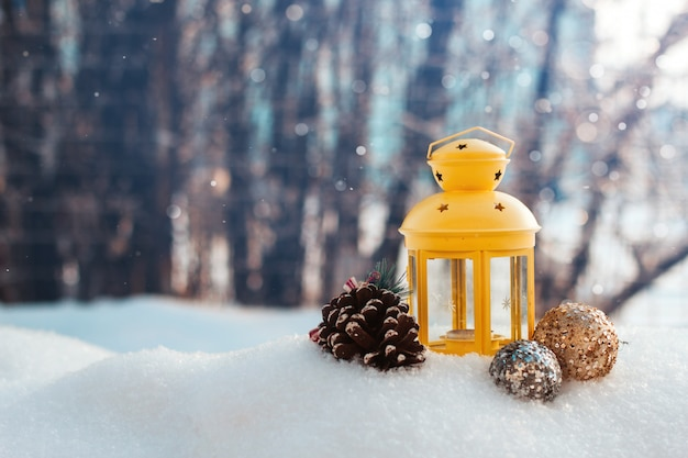Lanterna gialla di natale e giocattoli del nuovo anno nello spazio della copia della neve.