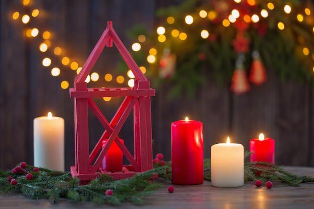 Lanterna in legno con candele e rami di natale su legno