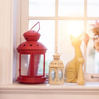 Lanterne d'annata rosse con il gatto ceramico sulla finestra alla luce di sera