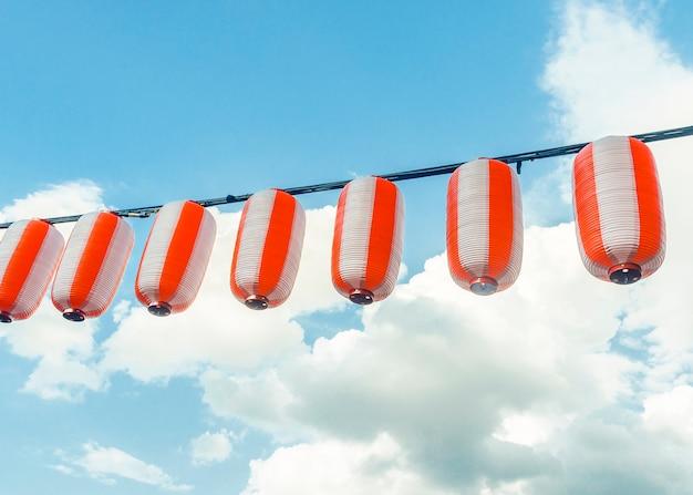 Lanterne giapponesi rosso-bianche di carta chochin che appende sul cielo blu