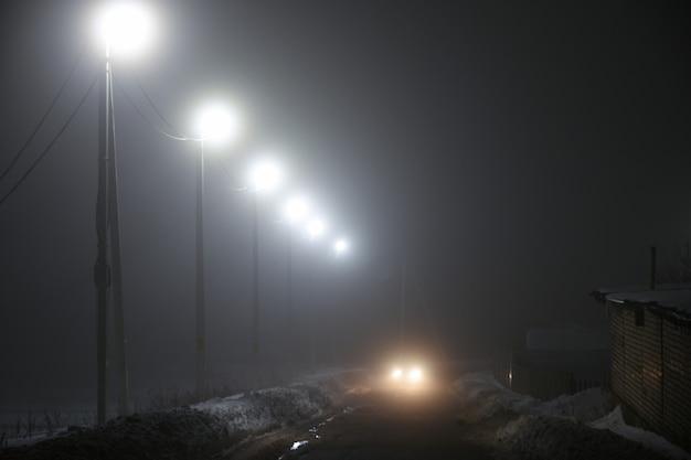 Lanterne lungo la strada di notte nella nebbia