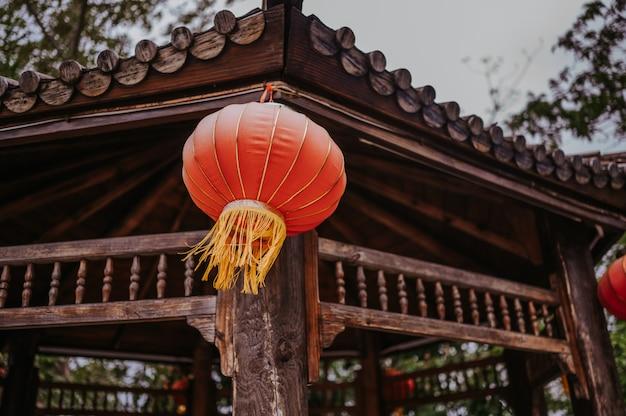 Lanterne rosse cinesi di viaggio della cina che appendono su una pagoda o su un gazebo di legno nel parco naturale per l'insegna lunare cinese di celebrazione del nuovo anno