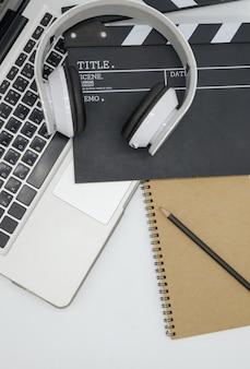 Laptop, auricolare, ciak film, blocco note su sfondo bianco