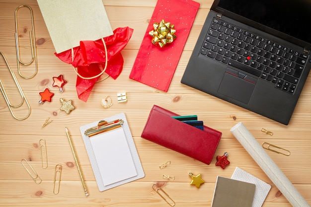 Laptop, carte di credito, borsa e decorazioni natalizie. shopping natalizio online, acquisto di regali