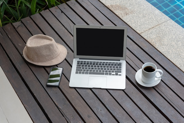 Laptop e cappello in piscina.