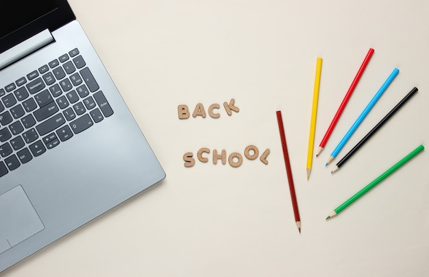 Laptop e matite colorate con lettere in legno