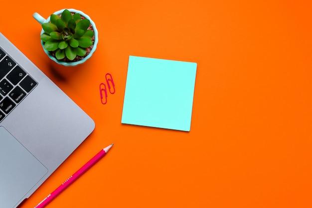 Laptop, fiori, adesivi, graffette, articoli di cancelleria su lussureggiante color lava.