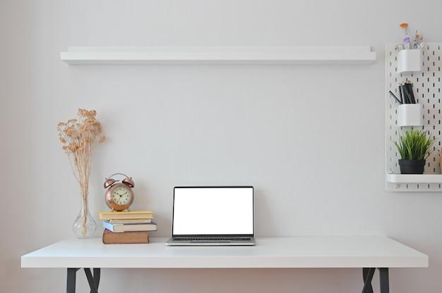 Laptop, libri, fiori secchi, orologio, matita e vaso con ripiani e piolo in ufficio.