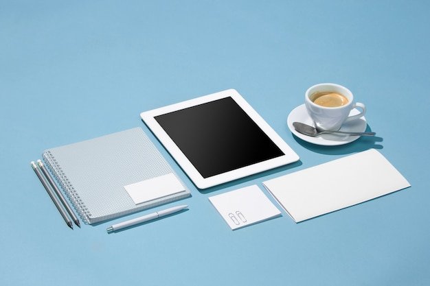 Laptop, penne, telefono, nota con schermo bianco sul tavolo
