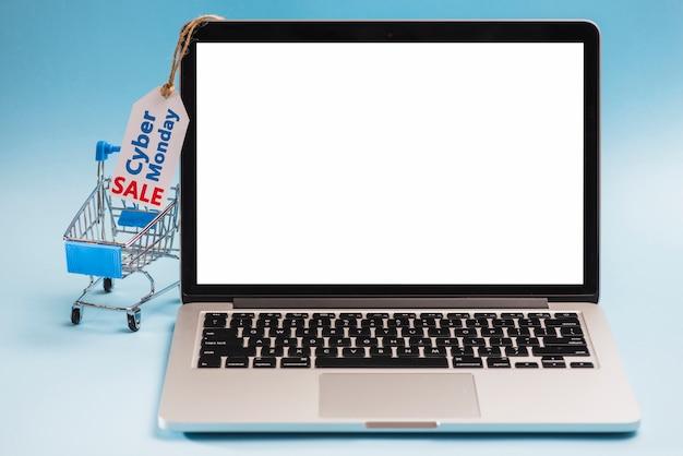 Laptop vicino carrello della spesa ed etichetta