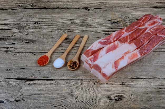 Lardo crudo fresco del maiale con le spezie per marinare su un bordo di legno di taglio.