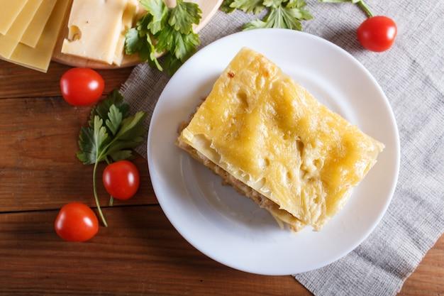 Lasagna con carne macinata e formaggio su legno marrone.
