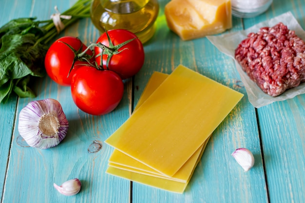 Lasagna, pomodori, carne macinata e altri ingredienti. fondo in legno blu. cucina italiana.