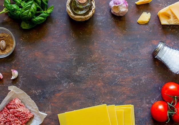 Lasagna, pomodori, carne macinata e altri ingredienti. sfondo scuro cucina italiana.