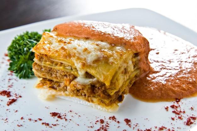 Lasagne dorate con carne, pomodori, salsa di formaggio e pasta a strati alternati su una tavola di legno guarnita con basilico