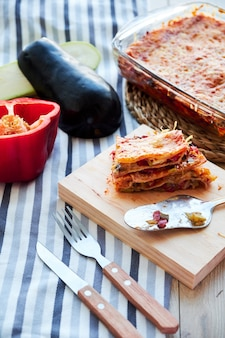 Lasagne vegetariane fatte in casa molto gustose con melanzane e pomodori, besciamella sulla tavola di legno.