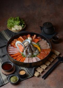 Lato di manzo guarnito con sesamo, e crostacei con gamberi disposti sul vassoio combinato con verdure per griglia sul tavolo.