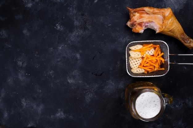 Lato di un bicchiere di birra, snack e coscia di pollo affumicato su uno sfondo nero