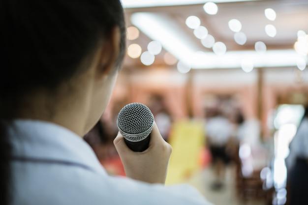 Lato posteriore del discorso astuto della donna di affari e parlare con il microfono