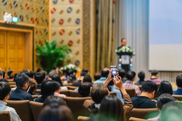 Lato posteriore del pubblico che scatta foto con il cellulare l'altoparlante con podio e presentazione