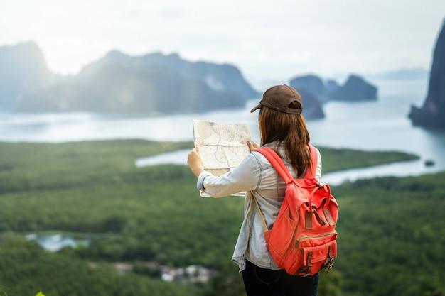 Lato posteriore del viaggiatore asiatico della donna che osserva la mappa per il viaggio con lo zaino in spalla a fantastico