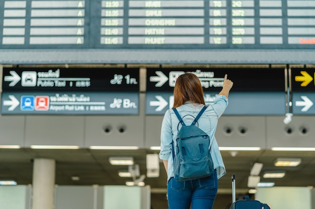 Lato posteriore del viaggiatore asiatico della donna con i bagagli che stanno sopra il bordo di volo per la registrazione