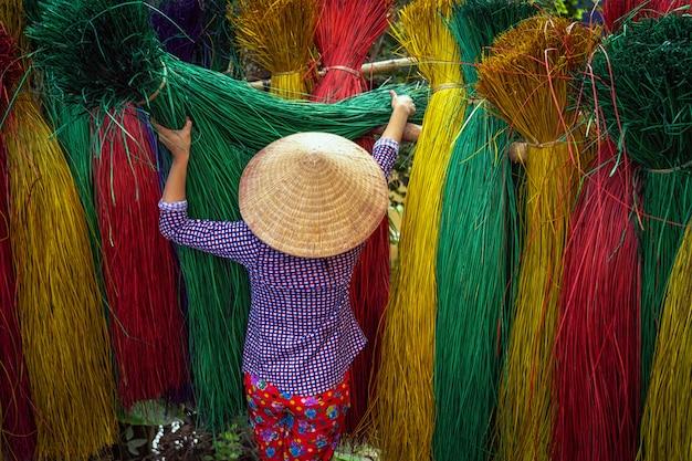 Lato posteriore dell'artigiano femminile vietnamita che asciuga le stuoie tradizionali del vietnam
