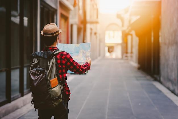 Lato posteriore dell'uomo turistico che cerca giusta direzione con la mappa sulla strada